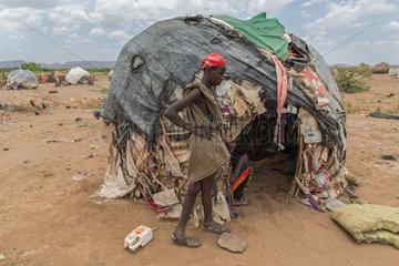 Kakuma  Kenia - Am Rande des Fluechtlingslagers Kakuma. Ein junger Mann steht vor seiner  von alten Plastikplanen  Decken  Kartons bedeckten Huette.