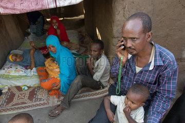 Kakuma  Kenia - Fluechtlingsfamilie mit Baby im Fluechtlingslager Kakuma. Ein Fluechtling telefoniert.