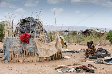 Kakuma  Kenia - Am Rande des Fluechtlingslagers Kakuma. Eine Frau sitzt verloren vor ihrer  von alten Plastikplanen bedeckten Huette.