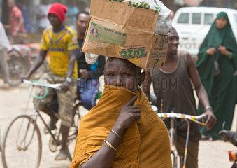 Kakuma  Kenia - Strassenszene mit Menschen auf einer belebten unbefestigten Strasse. Portraet einer Frau  die einen Karton auf dem Kopf traegt.