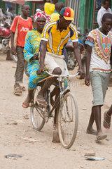 Kakuma  Kenia - Strassenszene. Mann und Frau fahren auf einer unbefestigten Strasse Fahrrad.