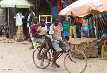 Kakuma  Kenia - Strassenszene. Drei Jungen fahren auf einer unbefestigten Strasse Fahrrad.