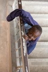 Nairobi  Kenia - Schuelerin in Schuluniform steht im Treppenhaus des St. John's Community Centers Pumwani und schaut zum Betrachter.