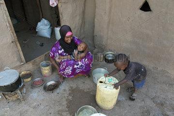 Kakuma  Kenia - Im Fluechtlingslager Kakuma sitzt eine Mutter mit ihren zwei Kindern vor einer Kochstelle.