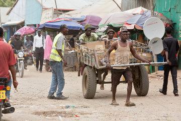 Kakuma  Kenia - Tageloehner ziehen einen grossen Transportanhaenger  beladen mit Waren auf einer belebten  unbefestigten Strasse.