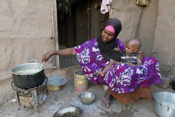 Kakuma  Kenia - Im Fluechtlingslager Kakuma sitzt eine Mutter mit Kind auf dem Arm vor einer Kochstelle und kocht.