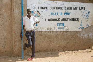 Kakuma  Kenia - Schueler lehnt im Fluechtlingslager Kakuma an einer Wand mit Aufschrift- I HAVE CONTROL OVER MY LIFE. THAT IS WHY I CHOOSE ABSTINENTE.