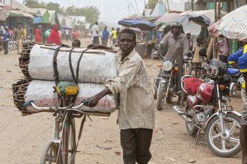 Kakuma  Kenia - Strassenszene. Ein Junge transportiert Holzkohlesaecke auf seinem Fahrrad auf einer belebten unbefestigten Strasse.