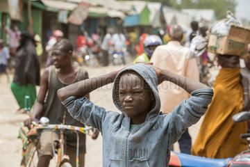 Kakuma  Kenia - Strassenszene mit Menschen auf einer belebten unbefestigten Strasse. Portraet eines nachdenklichen Jungen.