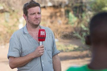 Kakuma  Kenia - Kai Feldhaus  Reporter und Journalist der Bild- Zeitung spricht im Fluechtlingslager Kakuma einen Aufsagetext ins Mikrofon.