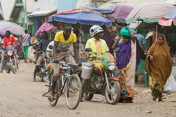 Kakuma  Kenia - Strassenszene mit Menschen  Motorraedern und Fahrrad. Verkehr auf einer belebten unbefestigten Strasse.