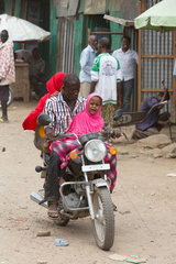 Kakuma  Kenia - Strassenszene. Eine Kleinfamilie faehrt auf einen Motorrad auf einer unbefestigten Strasse.