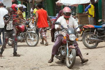 Kakuma  Kenia - Strassenszene mit Menschen und Motorraedern. Motorradverkehr auf einer belebten unbefestigten Strasse.