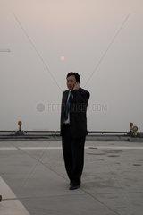 Peking  Geschaeftsmann am Handy