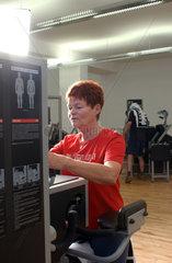 Seniorin an einem Geraet im Fitness-Studio