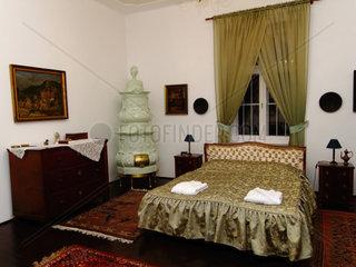 Schlafzimmer mit Kachelofen im Schlosshotel Pronay Ungarn