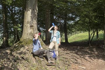 Wanderer erfrischen sich mit einem Getraenk im Wald
