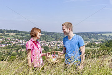 Junges Paar mit Picknickkorb im Kornfeld