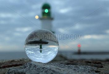 Warnemuende  Leuchttuerme an der Mole spiegeln sich bei Daemmerung in einer Glaskugel
