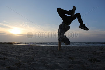 Wustrow  Deutschland - Silhouette  Junge macht am Strand einen Ueberschlag