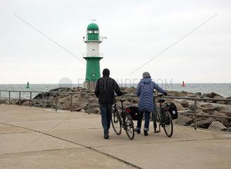 Warnemuende  Menschen wandern zum Leuchtturm auf der Westmole