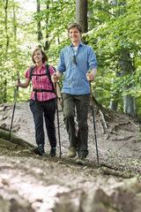 Junges Paar wandert mit Stoecken im Wald.