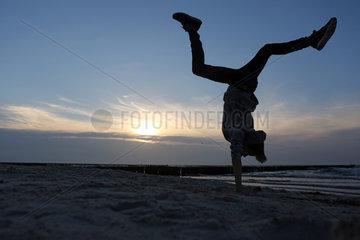Wustrow  Deutschland - Silhouette  Junge macht am Strand einen Handstand