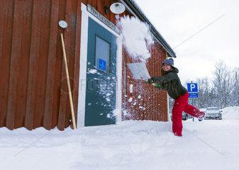 Junge Frau schippt Schnee auf einem Parkplatz