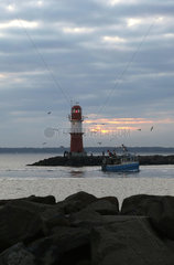 Warnemuende  Fischerboot bei Morgendaemmerung an der Ostmole