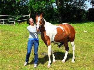 Junge Frau mit Pinto Warmblut Pferd auf der Koppel