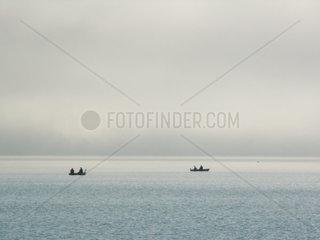 Fischerboote im Nebel auf dem Walchensee in den oberbayrischen Alpen.