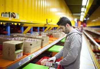 Junger Mann aus Syrien im Verteilzentrum des dm Markt im Weilerswist