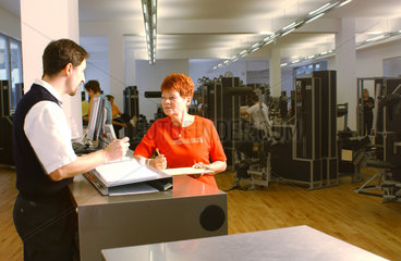 Seniorin im Fitness-Studio mit Trainer