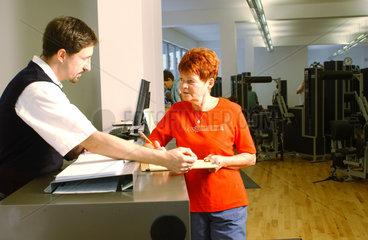 Seniorin im Fitness-Studio mit Trainer