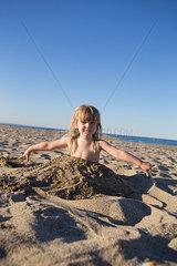 Maedchen spielt im Sand
