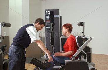 Seniorin an einem Geraet im Fitness-Studio mit Trainer