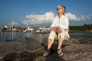 eine Frau sitzt auf der Mole im Hafen Timmendorf