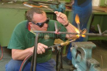 Auszubildender bei der Arbeit mit Metall