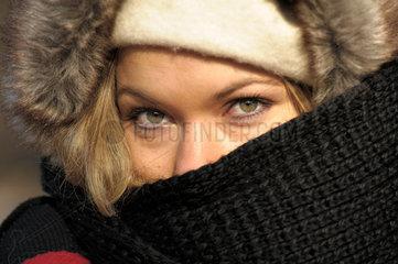 Junge Frau mit Schal vor Gesicht.