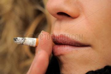 Junge Frau raucht eine Zigarette  Schaerfe auf Zigarette.