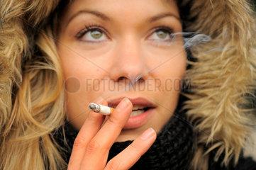 Junge Frau raucht eine Zigarette im Abendlicht  Schaerfe auf Hand.