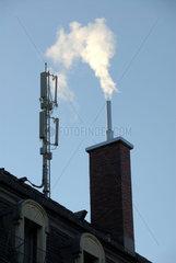 Handyantenne und Kamin (rauchend) auf einem Hausdach in Zuerich (CHE).