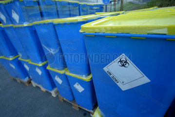 Biohazard Zeichen auf blauen Faessern mit medizinischen Abfaellen.