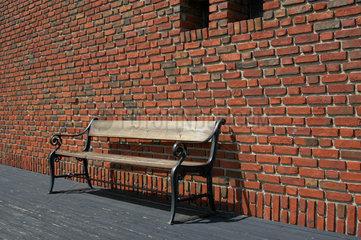Bank vor Backsteinmauer.