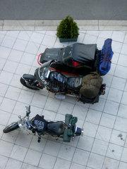 Zwei Reise - Motorraeder stehen auf einem Platz.