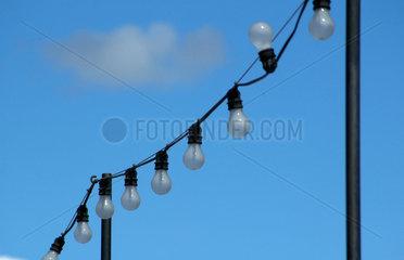 Gluehbirnenkette gegen Mittagshimmel.