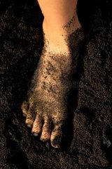Fuesse in schwarzem Lava - Sand.