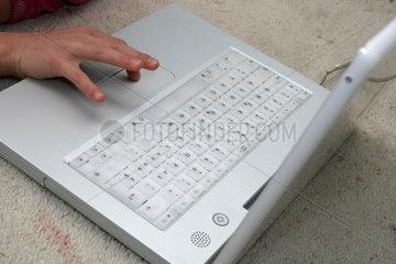 Eine Kinderhand schreibt auf einer Computertastatur.