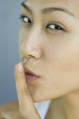 Woman holding finger against lips  portrait