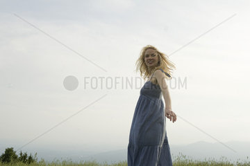 Young woman standing in meadow on breezy day  bubbles floating around her